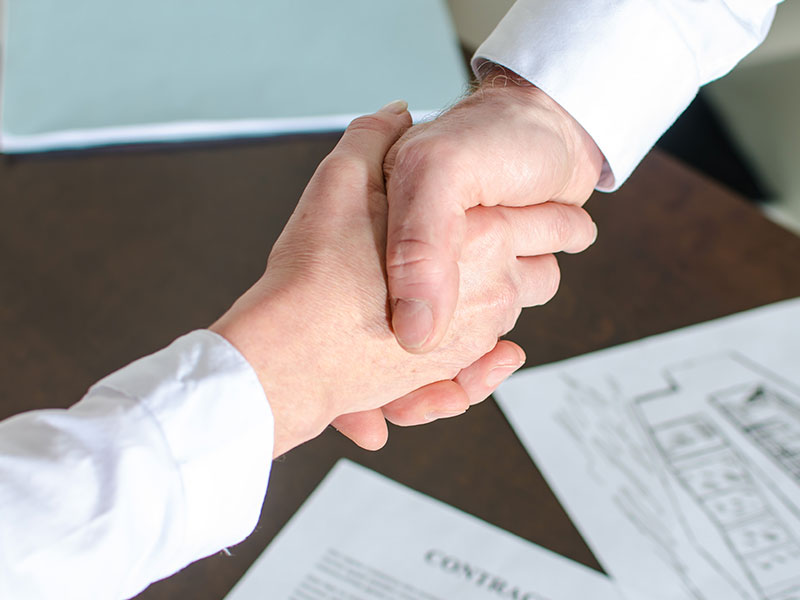 Hand Shake Over House Plans